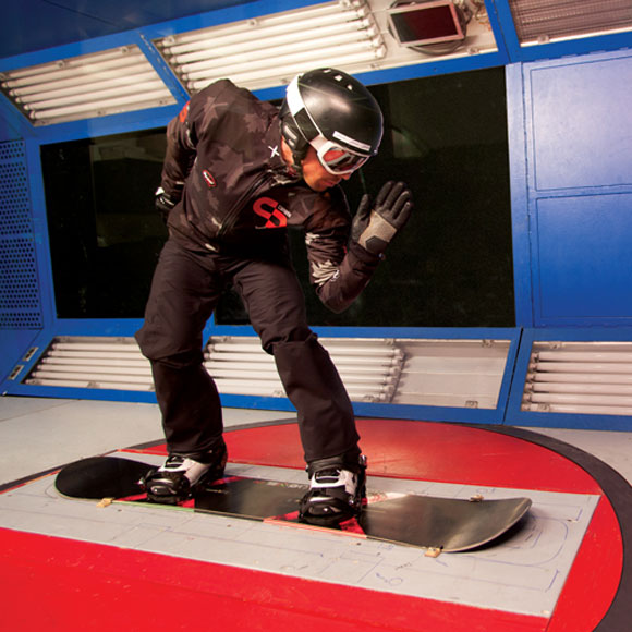 Male athlete standing in race position on a snowboard, wearing a suit, helmet and goggles